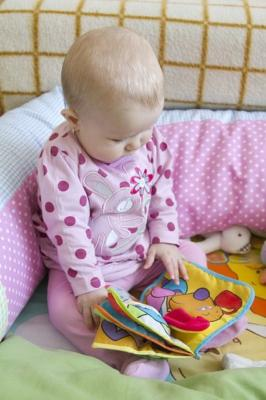Baby in pink reading a book made of cloth