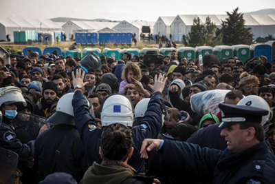 Image of many refugees being held back by guards