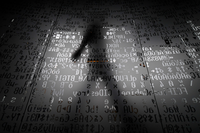 Image of a shadowy man and computer code