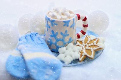 Image of mittens, holiday cookies and a mug of hot chocolate with marshmallows