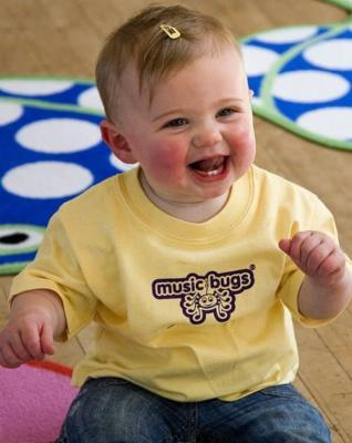 Image of toddler girl in a yellow shirt laughing