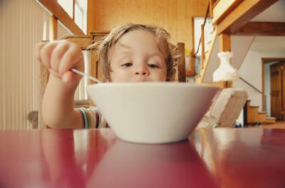 Image of young boy eating from large white bowl