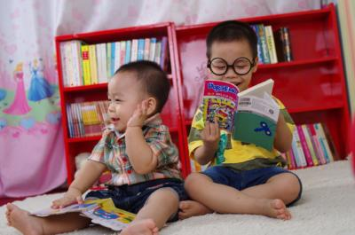 Image of two smiling babies reading books