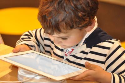 Image of very young boy playing with an ipad