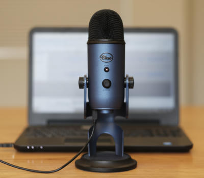Image of podcasting microphone in front of laptop computer
